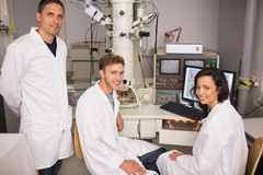 Biochemistry students using large microscope and computer Royalty Free Stock Photo
