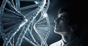 Biochemistry study and research . Mixed media. Man scientist and 3D rendering DNA molecule image at media screen Stock Photo