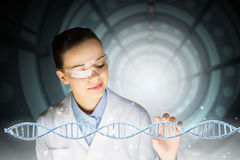Biochemistry study and research . Mixed media. Woman scientist and 3D rendering DNA molecule image at media screen Stock Photos