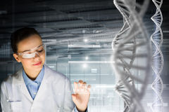 Biochemistry study and research . Mixed media. Woman scientist and 3D rendering DNA molecule image at media screen Stock Image