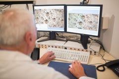 Biochimico che esamina le immagini microscopiche sul computer Immagini Stock Libere da Diritti