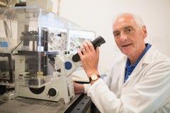 Biochimico che per mezzo di grandi microscopio e computer Immagini Stock Libere da Diritti