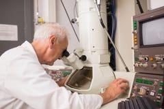 Biochimico che per mezzo di grandi microscopio e computer Fotografia Stock Libera da Diritti