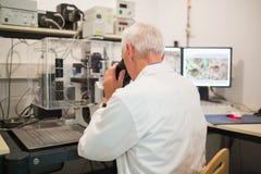 Biochimico che per mezzo di grandi microscopio e computer Immagini Stock