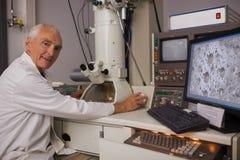 Biochimico che per mezzo di grandi microscopio e computer Fotografie Stock