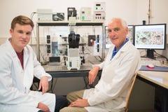 Biochimico che per mezzo di grandi microscopio e computer con lo studente Fotografia Stock Libera da Diritti