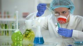 Biochimico che versa liquido oleoso in tubo con la sostanza blu e che controlla reazione stock footage