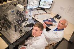 Biochimico e studente che esaminano le immagini microscopiche sul computer Fotografie Stock Libere da Diritti