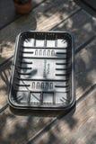 Biodegradable черный пакет подноса на деревянной предпосылке стоковые изображения