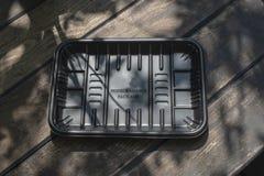 Biodegradable черный пакет подноса на деревянной предпосылке стоковая фотография rf
