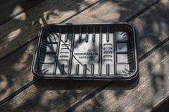 Biodegradable черный пакет подноса на деревянной предпосылке стоковые фотографии rf