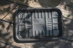 Biodegradable черный пакет подноса на деревянной предпосылке стоковое фото rf