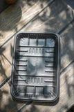 Biodegradable черный пакет подноса на деревянной предпосылке стоковое фото