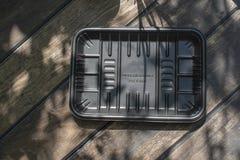 Biodegradable черный пакет подноса на деревянной предпосылке стоковое изображение