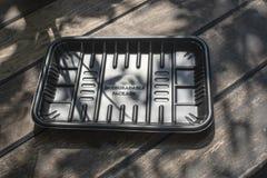 Biodegradable черный пакет подноса на деревянной предпосылке стоковая фотография