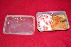 Biodegradable food packaging for take-away food. A selection of Indian takeaway dishes in plastic containers on a red table. It applies more particularly to Royalty Free Stock Images
