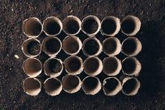 Biodegradable peat pot on greenhouse compost humus soil stock image