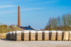 Biofuel and chimney. Biofuel as stacked birch wood on pallets. Smoke stack and roof of factory in background. Blue sky and some trees behind fuel stock images