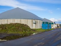 Biogas energy plant on farm in countryside with blue sky, Schleswig-Holstein, Germany.  stock photo