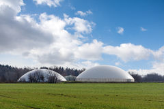 Biogas plant behind a wide field against blue sky Royalty Free Stock Photos