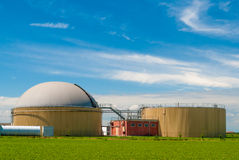 Biogas plant. A biogas plant in a green field with blue sky in the background Royalty Free Stock Image