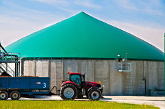 Biogas plant. Red tractor in forn of a biogas plant Royalty Free Stock Photos