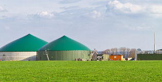 Biogas production. Biogas plant on green farmland royalty free stock photos