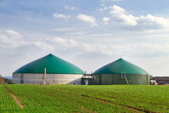 Biogas production. Biogas plant on green farmland Royalty Free Stock Photo