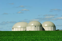BioGas tanks. Three biogas tanks between green fields Royalty Free Stock Photo