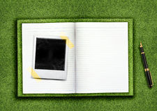 Biography. Curriculum vitae concept, blank opened book and empty photo on the green grassland and pen Royalty Free Stock Images