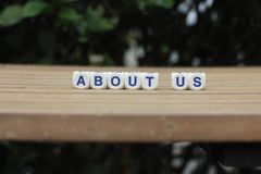 About us. Biography cube letters on horizontal wood plank leaf background Stock Photos