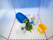 Biohazard disaster. Upper view of two specialists wearind white protection suits and gas masks collecting samples from a liquid spilling from a blue barrel, in a Stock Images