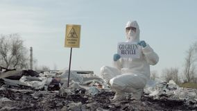 Biohazard Emergency, Hazmat biologist into Protective Costume shows sign go green recycle on rubbish dump with pointer