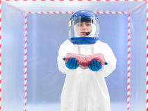 Biohazard geared person presenting raw meat Stock Photos