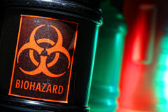 Biohazard Label on Dangerous Waste Container. Grunge biohazard universal symbol danger warning label on a dangerous toxic hazardous waste black container in a Stock Images