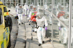 Biohazard medical team walking to building. Biohazard team with stretcher wear protective uniform walking outside building Stock Photography