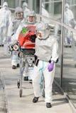 Biohazard medisch team met brancard buiten de bouw stock afbeelding