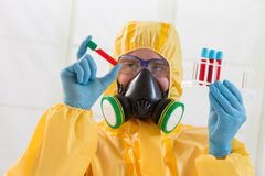 Biohazard. Scientist wearing protective suit and examining sample Stock Image
