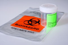 Biohazard specimen bag and cup. A plastic bag labeled Biohazard Specimen Bag and a specimen cup isolated on white background Royalty Free Stock Photo