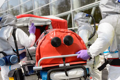 Biohazard team pushing stretcher towards chamber Stock Photos
