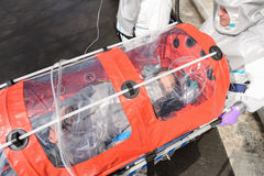 Biohazard team with virus patient in stretcher Royalty Free Stock Images