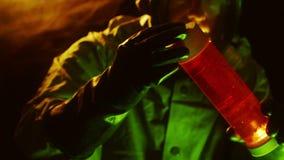 biohazardtech som kontrollerar en liten medicinflaska av röd flytande stock video