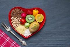 Biokost auf einer roten Herzplatte nährt abstraktes Stillleben Stockfotos