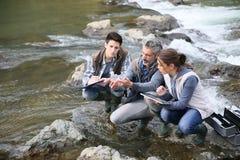 Biolog med studenter som testar flodvatten royaltyfri bild