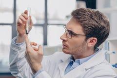 Biolog med växten i flaska arkivbild