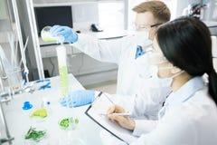 Biologen, die Experiment mit grüner Gemüseprobe leiten stockbild
