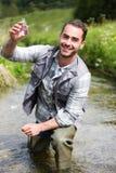 Biologen tar en prövkopia i en flod för att göra något prov royaltyfri foto