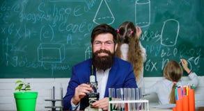 Biologi spelar roll, i att f?rst? av komplexa former av liv Skolal?rare av biologi Skäggigt lärarearbete för man med royaltyfri bild