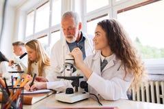 Biologia d'istruzione dell'insegnante senior agli studenti in laboratorio Immagine Stock