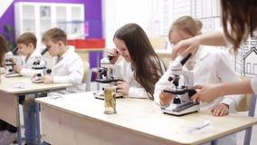 Biologia da escola primária, classe de química - crianças que olham através do microscópio video estoque